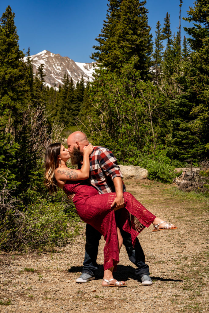 A man wearing plaid dipping his fiance in a red dress in front of a mountain. Photo by Gabby Jockers Photography. colorado engagement photography, colorado engagement photos, colorado engagement session, brainard lake engagement photos, brainard lake engagement session, colorado photography, brainard lake engagement photos, mountain engagement photos, lake engagement photos, mountain engagement session, hiking engagement, adventure photos, adventure session, couples photos, morning engagement photos