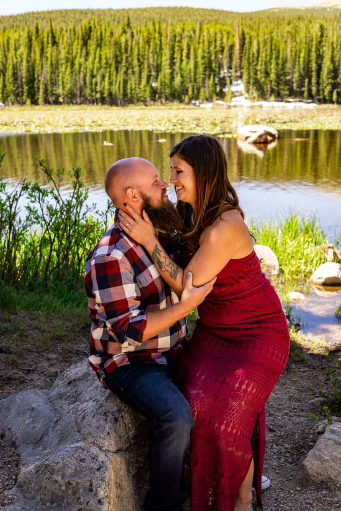 A woman in a red dress sitting on her fiance's lap in front of a lake while they smile at each other. Photo by Gabby Jockers Photography. colorado engagement photography, colorado engagement photos, colorado engagement session, brainard lake engagement photos, brainard lake engagement session, colorado photography, brainard lake engagement photos, mountain engagement photos, lake engagement photos, mountain engagement session, hiking engagement, adventure photos, adventure session, couples photos, morning engagement photos