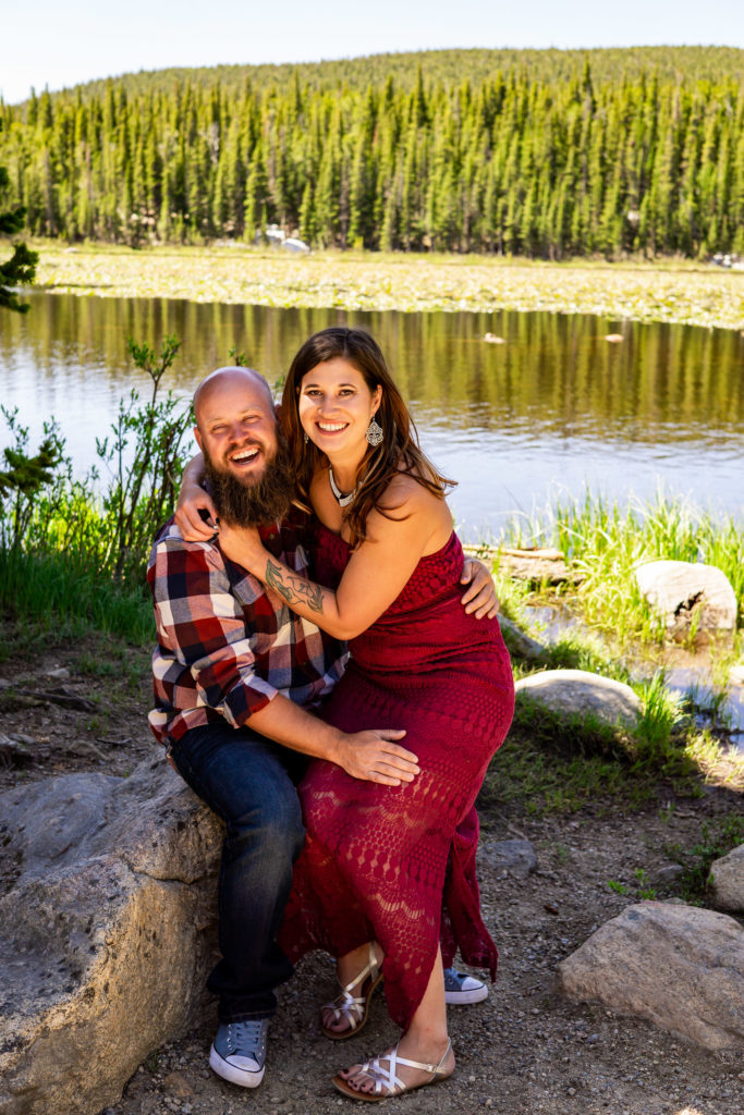 A woman in a red dress sitting on her fiance's lap in front of a lake while they both laugh. Photo by Gabby Jockers Photography. colorado engagement photography, colorado engagement photos, colorado engagement session, brainard lake engagement photos, brainard lake engagement session, colorado photography, brainard lake engagement photos, mountain engagement photos, lake engagement photos, mountain engagement session, hiking engagement, adventure photos, adventure session, couples photos, morning engagement photos