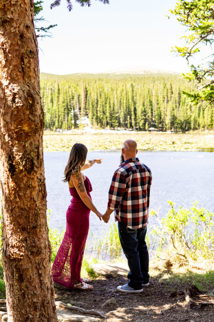 A man and woman holding hands and looking out over a sunny lake. Photo by Gabby Jockers Photography. colorado engagement photography, colorado engagement photos, colorado engagement session, brainard lake engagement photos, brainard lake engagement session, colorado photography, brainard lake engagement photos, mountain engagement photos, lake engagement photos, mountain engagement session, hiking engagement, adventure photos, adventure session, couples photos, morning engagement photos