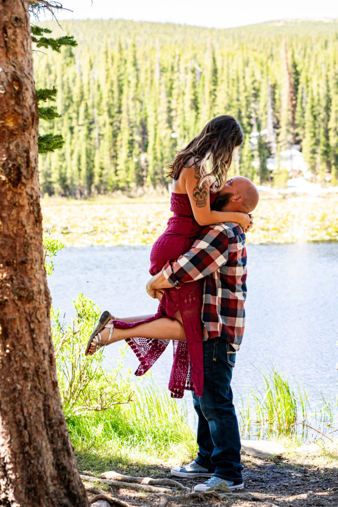 A man picks up his fiance in front of a sunny lake. Photo by Gabby Jockers Photography. colorado engagement photography, colorado engagement photos, colorado engagement session, brainard lake engagement photos, brainard lake engagement session, colorado photography, brainard lake engagement photos, mountain engagement photos, lake engagement photos, mountain engagement session, hiking engagement, adventure photos, adventure session, couples photos, morning engagement photos