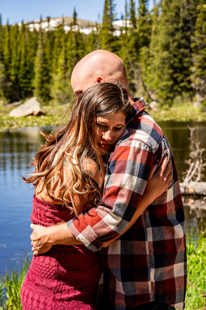 A newly engaged couple in a quiet embrace in front of Red Rock Lake and a mountain in Colorado. Photo by Gabby Jockers Photography. colorado engagement photography, colorado engagement photos, colorado engagement session, brainard lake engagement photos, brainard lake engagement session, colorado photography, brainard lake engagement photos, mountain engagement photos, lake engagement photos, mountain engagement session, hiking engagement, adventure photos, adventure session, couples photos, morning engagement photos