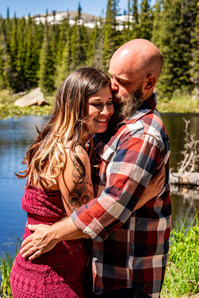 A newly engaged couple cuddling and laughing together and embracing in front of Red Rock Lake and a mountain in Colorado. Photo by Gabby Jockers Photography. colorado engagement photography, colorado engagement photos, colorado engagement session, brainard lake engagement photos, brainard lake engagement session, colorado photography, brainard lake engagement photos, mountain engagement photos, lake engagement photos, mountain engagement session, hiking engagement, adventure photos, adventure session, couples photos, morning engagement photos
