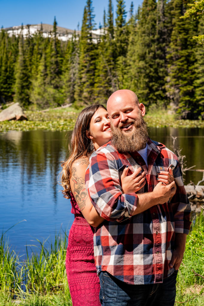 A newly engaged couple laughing together and embracing in front of Red Rock Lake and a mountain in Colorado. Photo by Gabby Jockers Photography. colorado engagement photography, colorado engagement photos, colorado engagement session, brainard lake engagement photos, brainard lake engagement session, colorado photography, brainard lake engagement photos, mountain engagement photos, lake engagement photos, mountain engagement session, hiking engagement, adventure photos, adventure session, couples photos, morning engagement photos