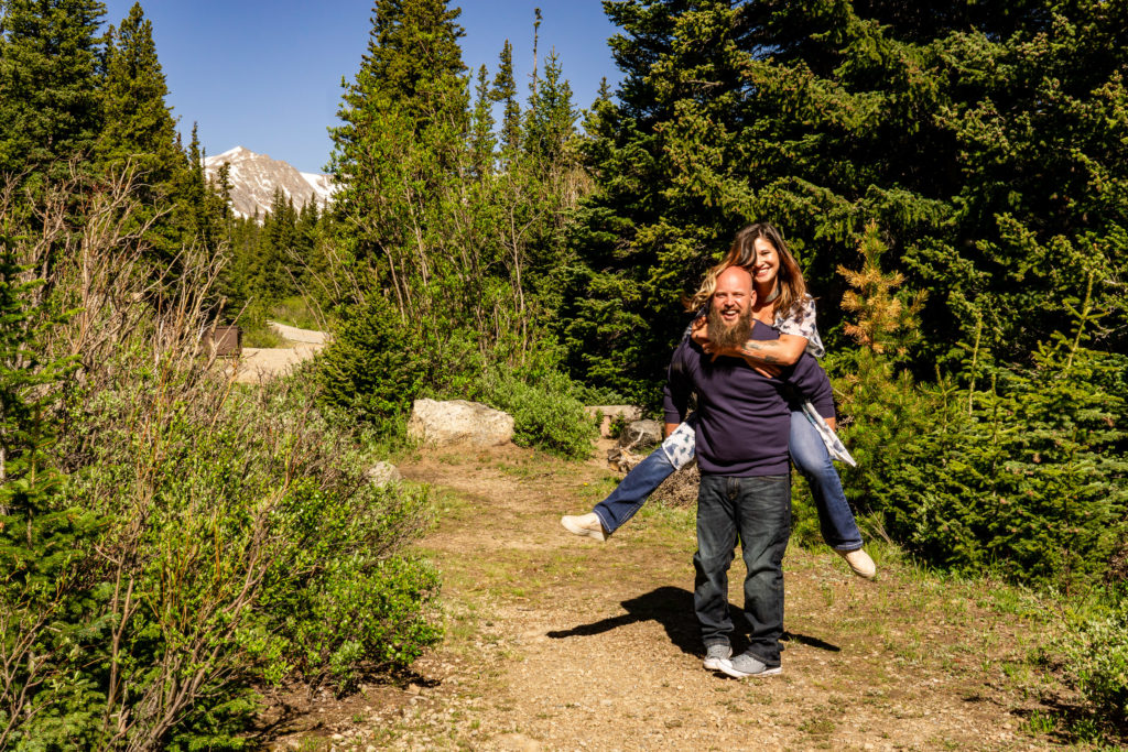 A couple doing piggyback rides in front of a majestic mountain in Colorado. Photo by Gabby Jockers Photography. colorado engagement photography, colorado engagement photos, colorado engagement session, brainard lake engagement photos, brainard lake engagement session, colorado photography, brainard lake engagement photos, mountain engagement photos, lake engagement photos, mountain engagement session, hiking engagement, adventure photos, adventure session, couples photos, morning engagement photos