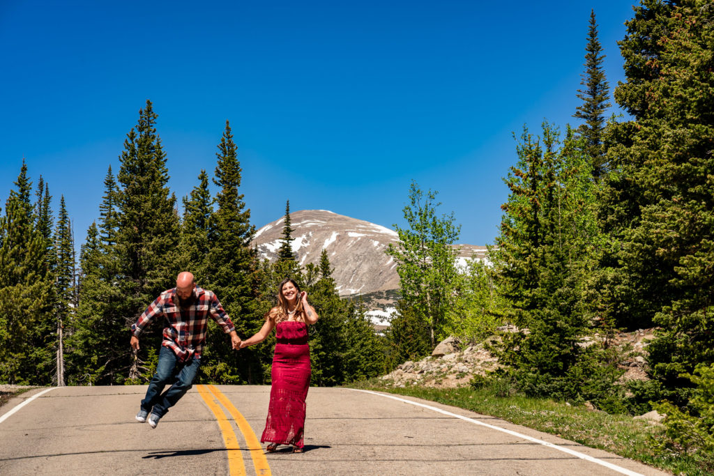 A man and woman walking down a road in front of a majestic Colorado mountain. They're holding hands and the guy is jumping up kicking his heels. Photo by Gabby Jockers Photography. colorado engagement photography, colorado engagement photos, colorado engagement session, brainard lake engagement photos, brainard lake engagement session, colorado photography, brainard lake engagement photos, mountain engagement photos, lake engagement photos, mountain engagement session, hiking engagement, adventure photos, adventure session, couples photos, morning engagement photos
