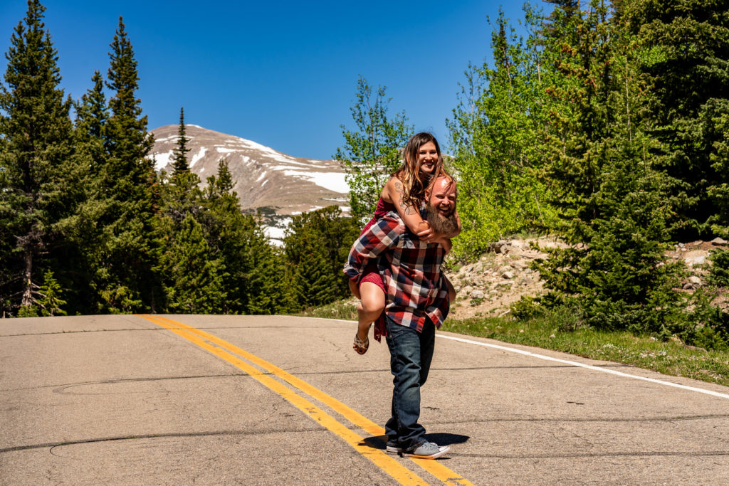 A newly engaged couple doing piggypacks in front of a majestic mountain in Colorado. Photo by Gabby Jockers Photography. colorado engagement photography, colorado engagement photos, colorado engagement session, brainard lake engagement photos, brainard lake engagement session, colorado photography, brainard lake engagement photos, mountain engagement photos, lake engagement photos, mountain engagement session, hiking engagement, adventure photos, adventure session, couples photos, morning engagement photos