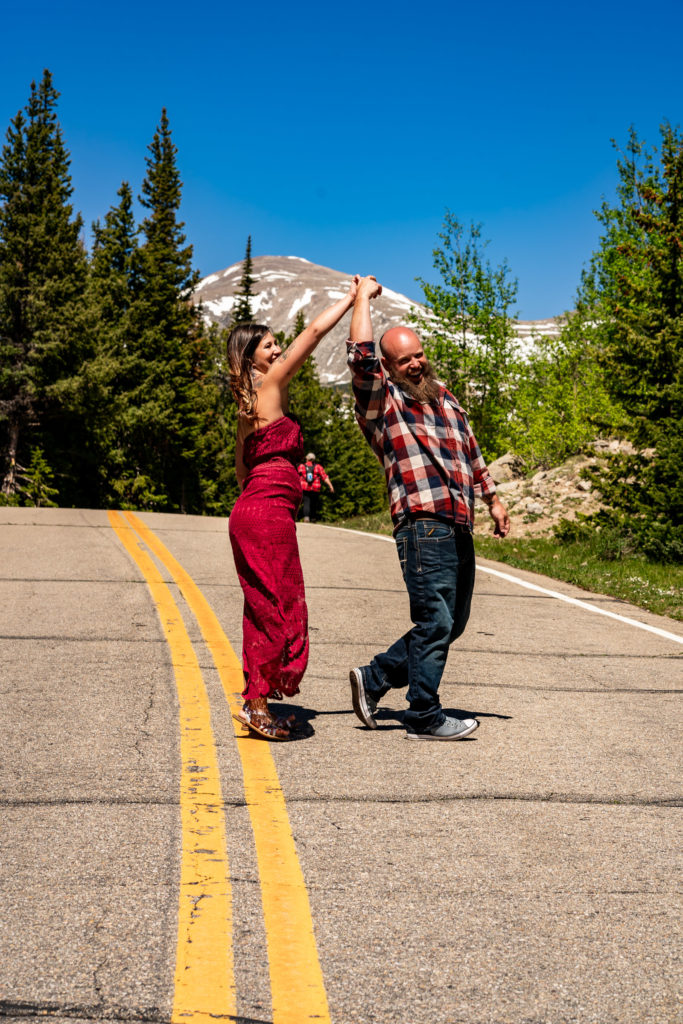 A man twirling his fiance on a road in front of a majestic mountain in Colorado. Photo by Gabby Jockers Photography. colorado engagement photography, colorado engagement photos, colorado engagement session, brainard lake engagement photos, brainard lake engagement session, colorado photography, brainard lake engagement photos, mountain engagement photos, lake engagement photos, mountain engagement session, hiking engagement, adventure photos, adventure session, couples photos, morning engagement photos