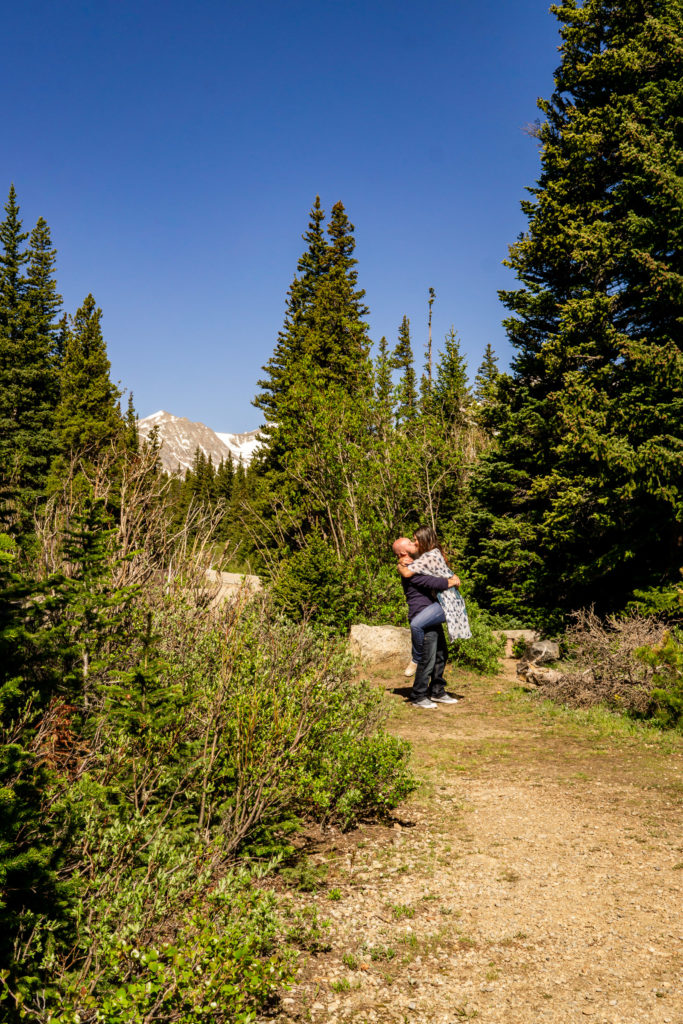 A man picks up his fiance for a big kiss in front of a mountain. Photo by Gabby Jockers Photography. colorado engagement photography, colorado engagement photos, colorado engagement session, brainard lake engagement photos, brainard lake engagement session, colorado photography, brainard lake engagement photos, mountain engagement photos, lake engagement photos, mountain engagement session, hiking engagement, adventure photos, adventure session, couples photos, morning engagement photos