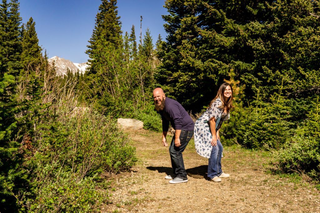 A silly couple bumpin' booties in front of a mountain. Photo by Gabby Jockers Photography. colorado engagement photography, colorado engagement photos, colorado engagement session, brainard lake engagement photos, brainard lake engagement session, colorado photography, brainard lake engagement photos, mountain engagement photos, lake engagement photos, mountain engagement session, hiking engagement, adventure photos, adventure session, couples photos, morning engagement photos