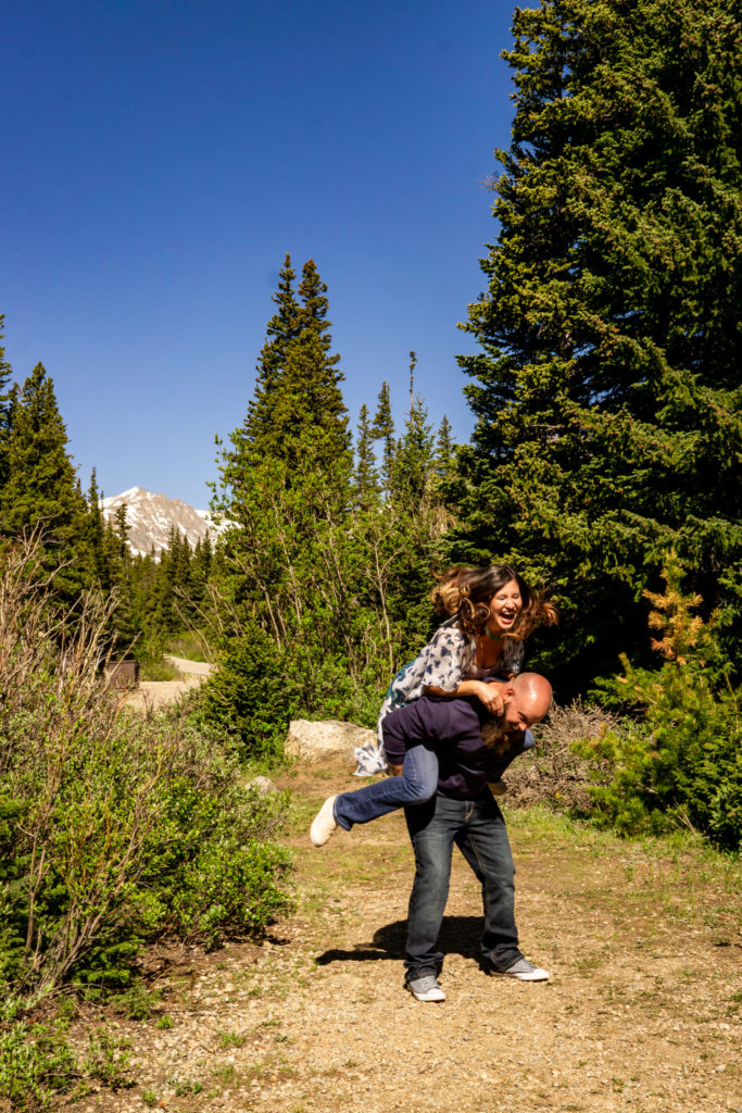 A silly playful couple doing piggyback rides in front of a mountain. Photo by Gabby Jockers Photography. colorado engagement photography, colorado engagement photos, colorado engagement session, brainard lake engagement photos, brainard lake engagement session, colorado photography, brainard lake engagement photos, mountain engagement photos, lake engagement photos, mountain engagement session, hiking engagement, adventure photos, adventure session, couples photos, morning engagement photos