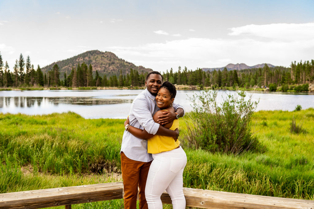 A couple embracing, laughing, smiling in front of a lush green lake with a mountain in the background. Photo by Gabby Jockers Photography. Rocky mountain national park engagement photography, Rocky mountain national park engagement photos, Rocky mountain national park engagement session, sprague lake engagement photos, sprague lake engagement session, estes park engagement, estes park engagement photos, adventure photos, adventure session, couples photos
