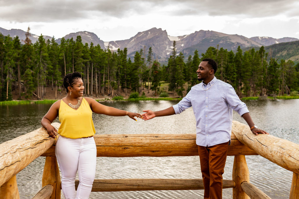 A couple standing on a pier over a mountain lake, hands reaching toward each other. Photo by Gabby Jockers Photography. Rocky mountain national park engagement photography, Rocky mountain national park engagement photos, Rocky mountain national park engagement session, sprague lake engagement photos, sprague lake engagement session, estes park engagement, estes park engagement photos, adventure photos, adventure session, couples photos