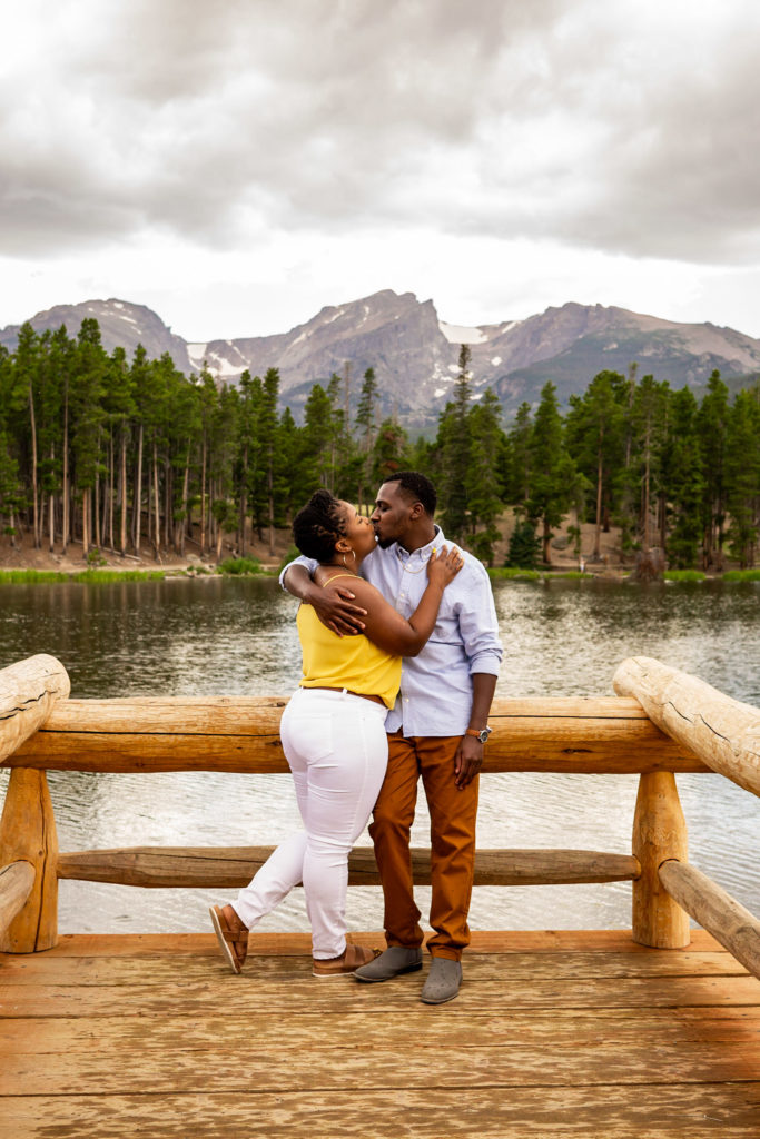 A newly engaged couple kissing in front of a lake and mountain background. Photo by Gabby Jockers Photography. Rocky mountain national park engagement photography, Rocky mountain national park engagement photos, Rocky mountain national park engagement session, sprague lake engagement photos, sprague lake engagement session, estes park engagement, estes park engagement photos, adventure photos, adventure session, couples photos