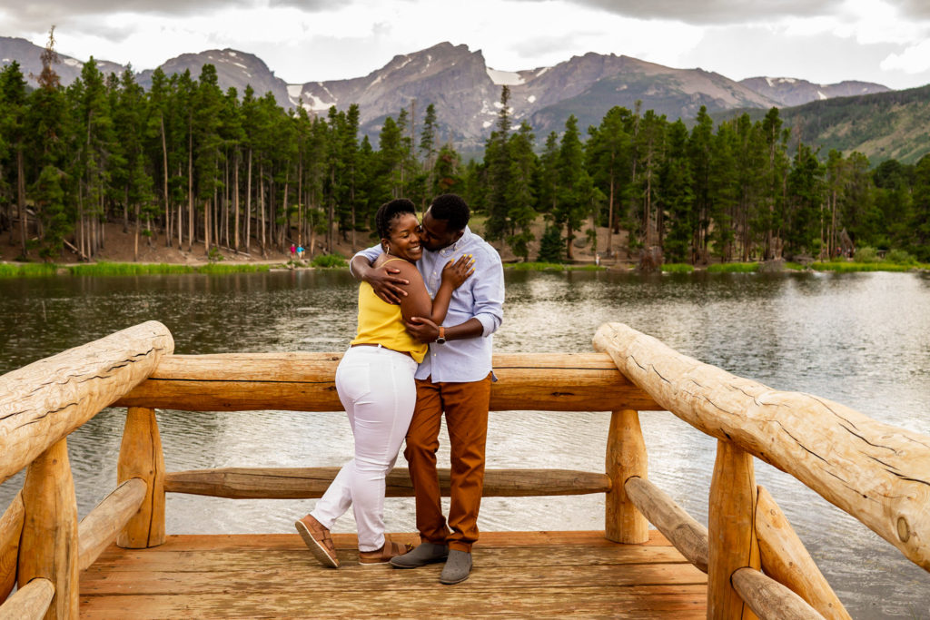 A newly engaged couple smiling and cuddling in front of a lake and mountain background. Photo by Gabby Jockers Photography. Rocky mountain national park engagement photography, Rocky mountain national park engagement photos, Rocky mountain national park engagement session, sprague lake engagement photos, sprague lake engagement session, estes park engagement, estes park engagement photos, adventure photos, adventure session, couples photos