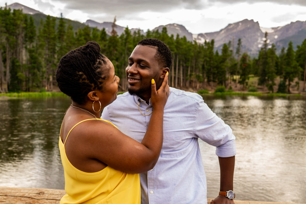 A newly engaged couple smiling at each other in front of a lake and mountain background. Photo by Gabby Jockers Photography. Rocky mountain national park engagement photography, Rocky mountain national park engagement photos, Rocky mountain national park engagement session, sprague lake engagement photos, sprague lake engagement session, estes park engagement, estes park engagement photos, adventure photos, adventure session, couples photos