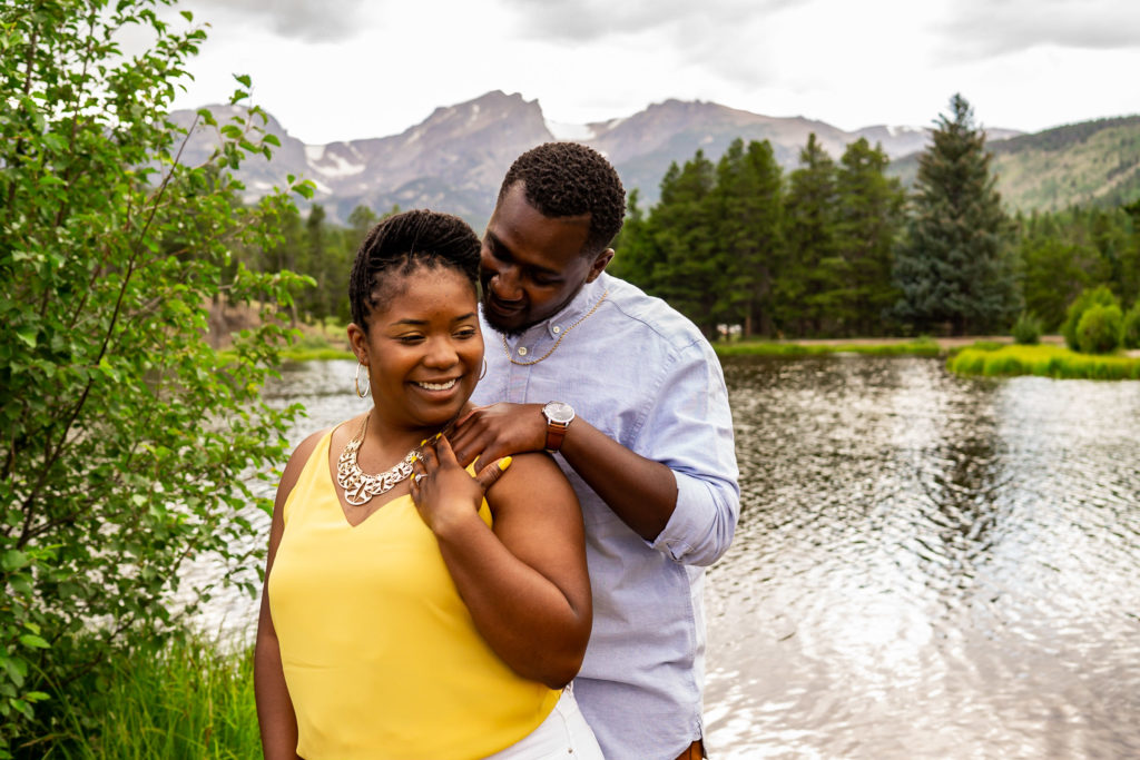 A happy engaged couple snuggling up in front a beautiful lake with mountain views. Photo by Gabby Jockers Photography. Rocky mountain national park engagement photography, Rocky mountain national park engagement photos, Rocky mountain national park engagement session, sprague lake engagement photos, sprague lake engagement session, estes park engagement, estes park engagement photos, adventure photos, adventure session, couples photos