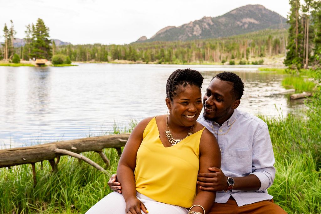 An engaged couple cuddling on a bench in front of a beautiful lake and mountain background. Photo by Gabby Jockers Photography. Rocky mountain national park engagement photography, Rocky mountain national park engagement photos, Rocky mountain national park engagement session, sprague lake engagement photos, sprague lake engagement session, estes park engagement, estes park engagement photos, adventure photos, adventure session, couples photos