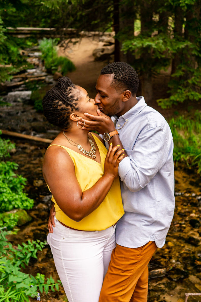 A man kisses his fiance passionately in a lush green forest by a creek. Photo by Gabby Jockers Photography. Rocky mountain national park engagement photography, Rocky mountain national park engagement photos, Rocky mountain national park engagement session, sprague lake engagement photos, sprague lake engagement session, estes park engagement, estes park engagement photos, adventure photos, adventure session, couples photos