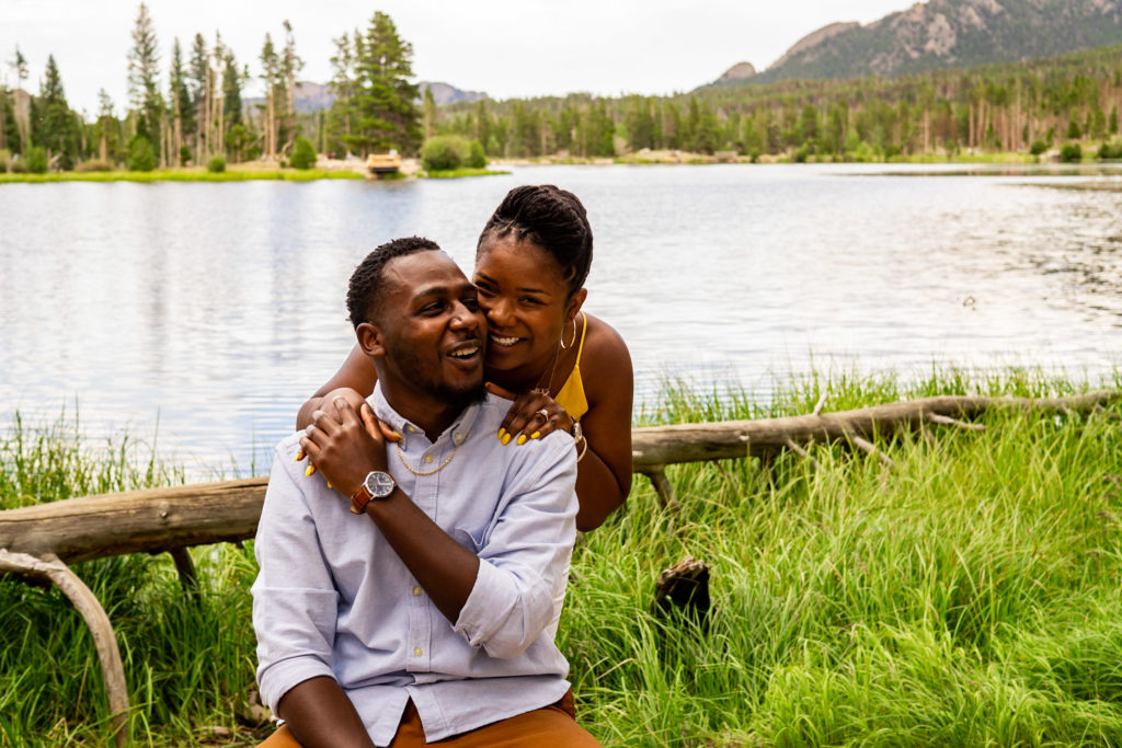 A couple laughing together in front of a lovely lake and mountain. Photo by Gabby Jockers Photography. Rocky mountain national park engagement photography, Rocky mountain national park engagement photos, Rocky mountain national park engagement session, sprague lake engagement photos, sprague lake engagement session, estes park engagement, estes park engagement photos, adventure photos, adventure session, couples photos