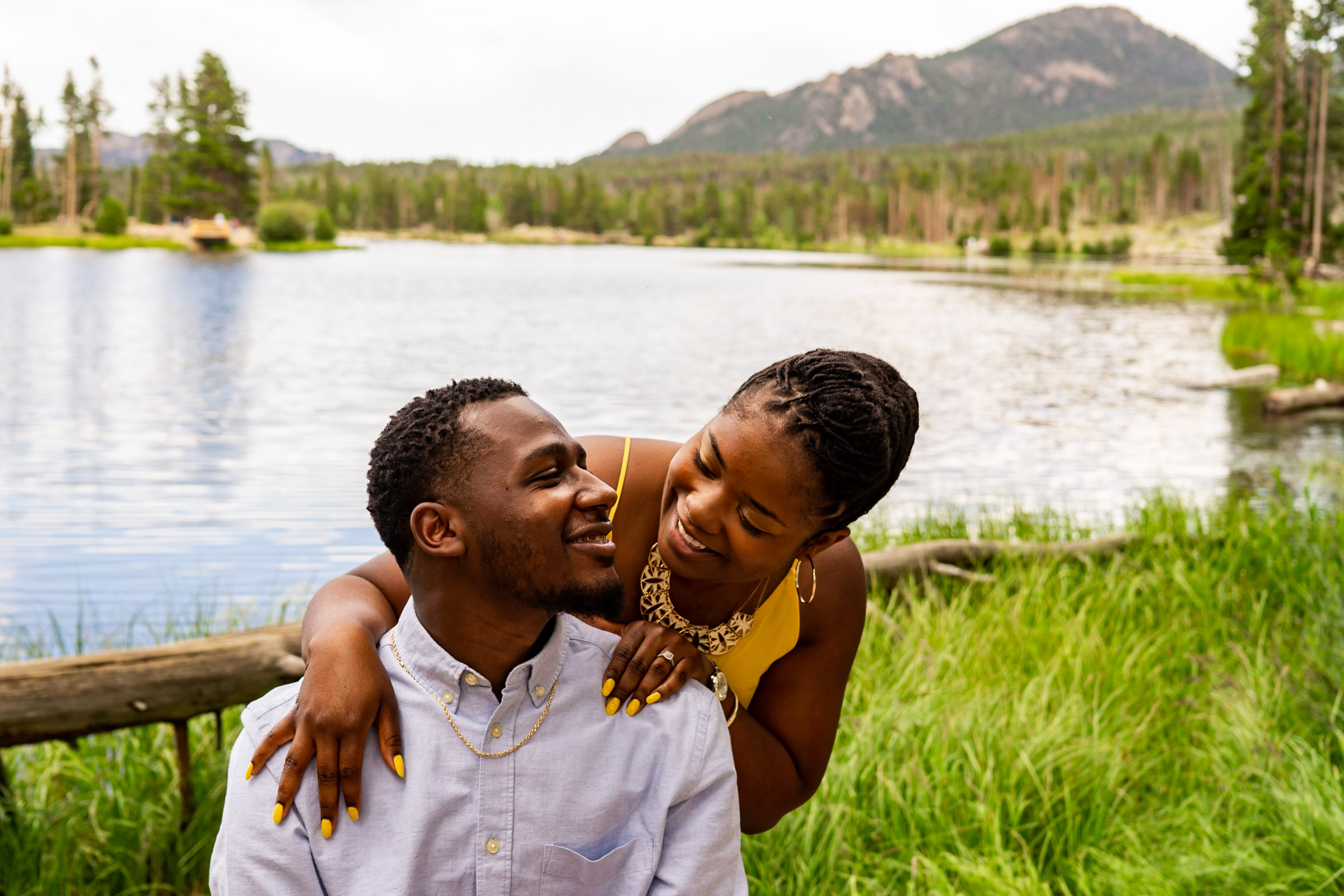 A woman's arms on her man's shoulder as he sits in front of a mountain lake. Photo by Gabby Jockers Photography. Rocky mountain national park engagement photography, Rocky mountain national park engagement photos, Rocky mountain national park engagement session, sprague lake engagement photos, sprague lake engagement session, estes park engagement, estes park engagement photos, adventure photos, adventure session, couples photos