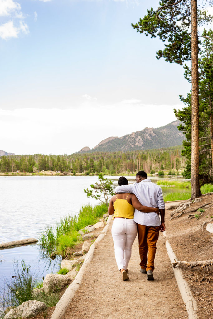 A couple walks down a beautiful lake trail with arms around each other. Photo by Gabby Jockers Photography. Rocky mountain national park engagement photography, Rocky mountain national park engagement photos, Rocky mountain national park engagement session, sprague lake engagement photos, sprague lake engagement session, estes park engagement, estes park engagement photos, adventure photos, adventure session, couples photos