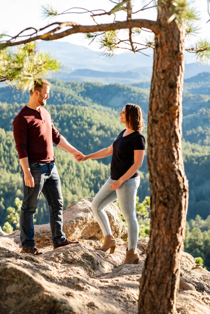 A cute couple holding hands and chatting to each other in front of a beautiful mountain vista. Photo by Gabby Jockers Photography. colorado engagement photography, colorado engagement photos, colorado engagement session, evergreen co engagement photos, evergreen co engagement session, colorado photography, evergreen co engagement photos, mountain engagement photos, mountain engagement session, sunset engagement photos, hiking engagement, adventure photos, adventure session, couples photos