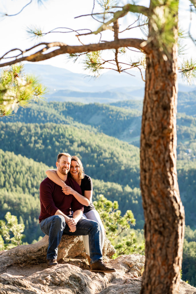 A newly engaged couple sitting side by side with the woman's arms looped around her fiance's neck. Photo by Gabby Jockers Photography. colorado engagement photography, colorado engagement photos, colorado engagement session, evergreen co engagement photos, evergreen co engagement session, colorado photography, evergreen co engagement photos, mountain engagement photos, mountain engagement session, sunset engagement photos, hiking engagement, adventure photos, adventure session, couples photos
