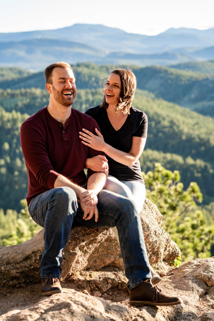 A newly engaged couple sitting, cuddling, and laughing as the wind blows at them on the top of a mountain. Photo by Gabby Jockers Photography. colorado engagement photography, colorado engagement photos, colorado engagement session, evergreen co engagement photos, evergreen co engagement session, colorado photography, evergreen co engagement photos, mountain engagement photos, mountain engagement session, sunset engagement photos, hiking engagement, adventure photos, adventure session, couples photos