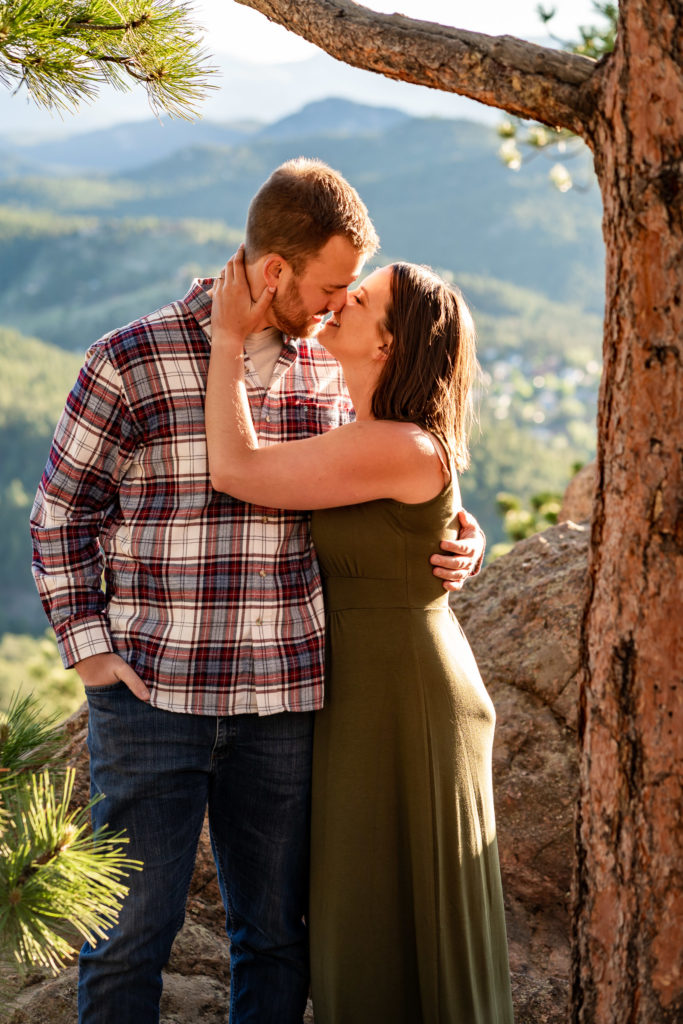 A man and woman cuddling underneath a tree in front of a mountain vista. Photo by Gabby Jockers Photography. colorado engagement photography, colorado engagement photos, colorado engagement session, evergreen co engagement photos, evergreen co engagement session, colorado photography, evergreen co engagement photos, mountain engagement photos, mountain engagement session, sunset engagement photos, hiking engagement, adventure photos, adventure session, couples photos