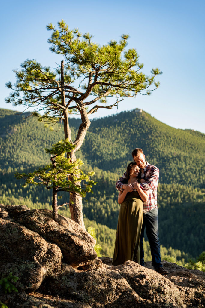 A man hugs his fiance from behind next to a beautiful tree in front of a mountain vista. Photo by Gabby Jockers Photography. colorado engagement photography, colorado engagement photos, colorado engagement session, evergreen co engagement photos, evergreen co engagement session, colorado photography, evergreen co engagement photos, mountain engagement photos, mountain engagement session, sunset engagement photos, hiking engagement, adventure photos, adventure session, couples photos
