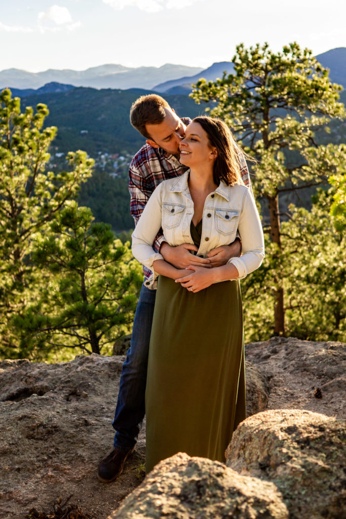 A man hugging his fiance from behind and kissing her on the cheek, making her smile brightly. Photo by Gabby Jockers Photography. colorado engagement photography, colorado engagement photos, colorado engagement session, evergreen co engagement photos, evergreen co engagement session, colorado photography, evergreen co engagement photos, mountain engagement photos, mountain engagement session, sunset engagement photos, hiking engagement, adventure photos, adventure session, couples photos