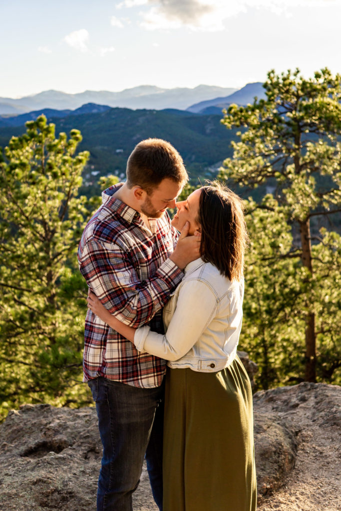 A newly engaged couple smiling and holding on to each other while the golden rays of sunshine light them up. Photo by Gabby Jockers Photography. colorado engagement photography, colorado engagement photos, colorado engagement session, evergreen co engagement photos, evergreen co engagement session, colorado photography, evergreen co engagement photos, mountain engagement photos, mountain engagement session, sunset engagement photos, hiking engagement, adventure photos, adventure session, couples photos