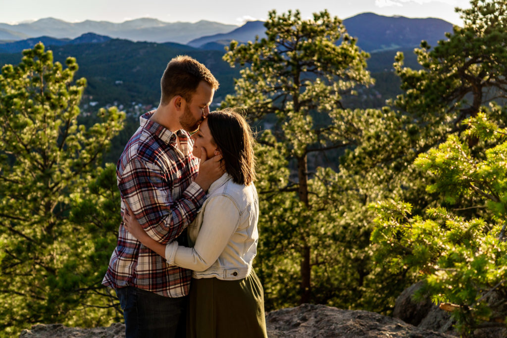 A man kissed his fiance's forehead as the golden sunset rays light them up. Photo by Gabby Jockers Photography. colorado engagement photography, colorado engagement photos, colorado engagement session, evergreen co engagement photos, evergreen co engagement session, colorado photography, evergreen co engagement photos, mountain engagement photos, mountain engagement session, sunset engagement photos, hiking engagement, adventure photos, adventure session, couples photos