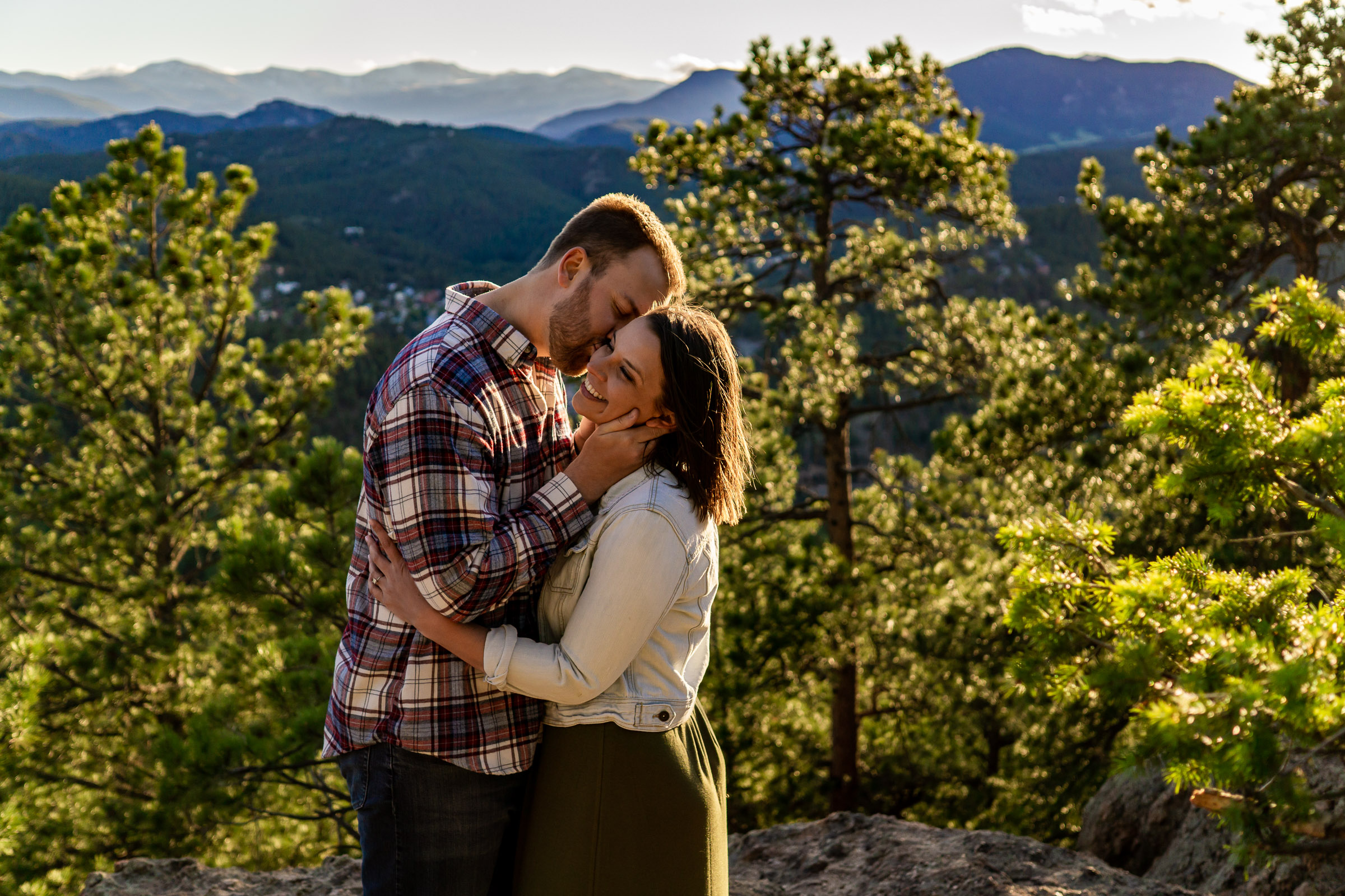 A man whispers something funny in his fiance's ear, making her giggle. Photo by Gabby Jockers Photography. colorado engagement photography, colorado engagement photos, colorado engagement session, evergreen co engagement photos, evergreen co engagement session, colorado photography, evergreen co engagement photos, mountain engagement photos, mountain engagement session, sunset engagement photos, hiking engagement, adventure photos, adventure session, couples photos