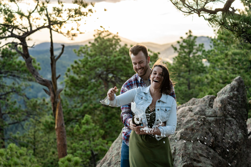 A couple celebrates their engagement by popping a bottle of sparkling wine in front of a mountain vista at sunset. Photo by Gabby Jockers Photography. colorado engagement photography, colorado engagement photos, colorado engagement session, evergreen co engagement photos, evergreen co engagement session, colorado photography, evergreen co engagement photos, mountain engagement photos, mountain engagement session, sunset engagement photos, hiking engagement, adventure photos, adventure session, couples photos
