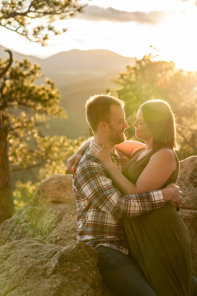 A newly engaged couple cuddling in each others arms in front of a mountain vista during a golden sunset. Photo by Gabby Jockers Photography. colorado engagement photography, colorado engagement photos, colorado engagement session, evergreen co engagement photos, evergreen co engagement session, colorado photography, evergreen co engagement photos, mountain engagement photos, mountain engagement session, sunset engagement photos, hiking engagement, adventure photos, adventure session, couples photos