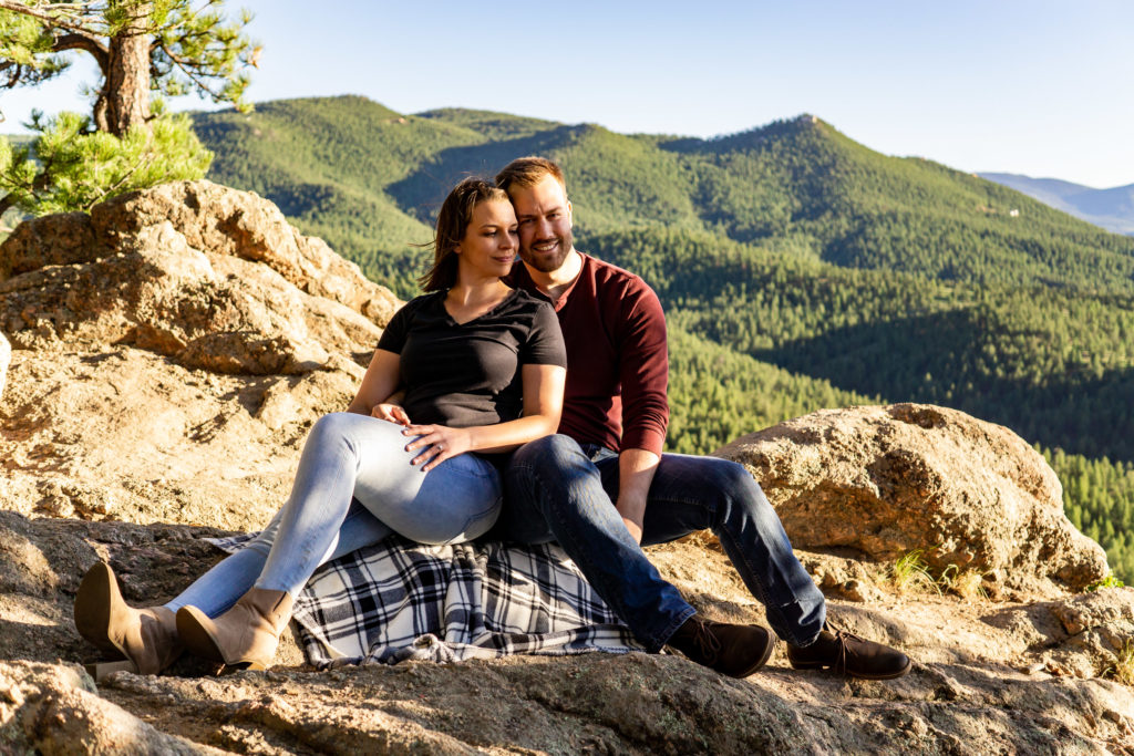A newly engaged couple cuddling on a blanket on a mountain. Photo by Gabby Jockers Photography. colorado engagement photography, colorado engagement photos, colorado engagement session, evergreen co engagement photos, evergreen co engagement session, colorado photography, evergreen co engagement photos, mountain engagement photos, mountain engagement session, sunset engagement photos, hiking engagement, adventure photos, adventure session, couples photos