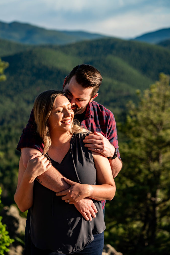A newly engaged couple snuggling up in the bright sun in front of green mountains. Photo by Gabby Jockers Photography. Mount falcon engagement photography, colorado engagement photos, colorado engagement session, mountain engagement photos, mountain session, colorado photography, outdoor engagement photos, outdoor engagement session, hiking engagement, adventure photos, adventure session, couples photos