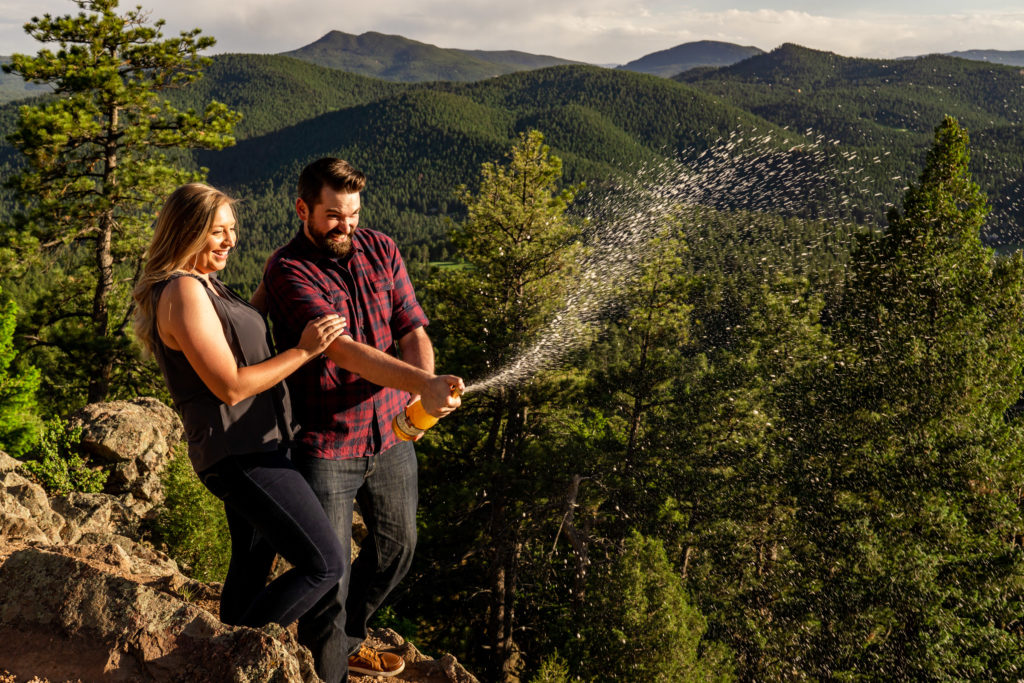 A newly engaged couple popping champagne in front of a mountain vista in Colorado. Photo by Gabby Jockers Photography. Mount falcon engagement photography, colorado engagement photos, colorado engagement session, mountain engagement photos, mountain session, colorado photography, outdoor engagement photos, outdoor engagement session, hiking engagement, adventure photos, adventure session, couples photos