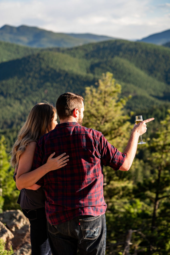 A newly engaged couple drink champagne while looking out over the green mountains of colorado. Photo by Gabby Jockers Photography. Mount falcon engagement photography, colorado engagement photos, colorado engagement session, mountain engagement photos, mountain session, colorado photography, outdoor engagement photos, outdoor engagement session, hiking engagement, adventure photos, adventure session, couples photos