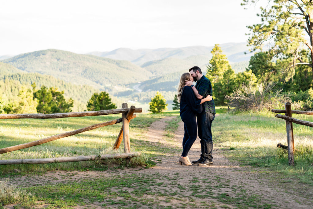 A man and woman kissing on a path leading to distant mountains. Photo by Gabby Jockers Photography. Mount falcon engagement photography, colorado engagement photos, colorado engagement session, mountain engagement photos, mountain session, colorado photography, outdoor engagement photos, outdoor engagement session, hiking engagement, adventure photos, adventure session, couples photos