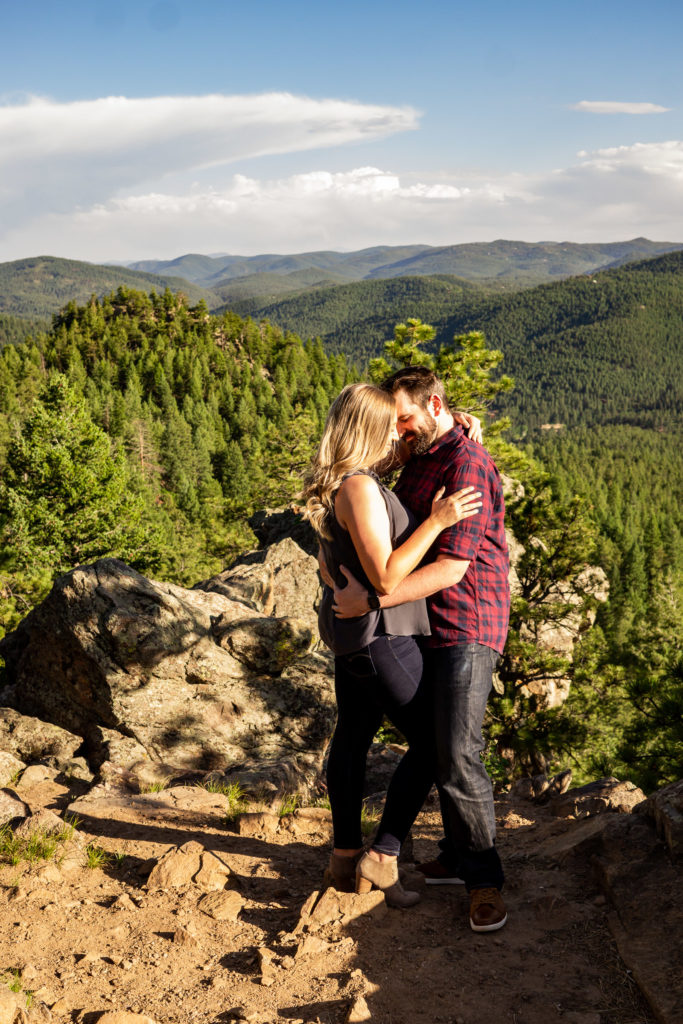 A couple in a passionate embrace in front of sunny, green mountains. Photo by Gabby Jockers Photography. Mount falcon engagement photography, colorado engagement photos, colorado engagement session, mountain engagement photos, mountain session, colorado photography, outdoor engagement photos, outdoor engagement session, hiking engagement, adventure photos, adventure session, couples photos