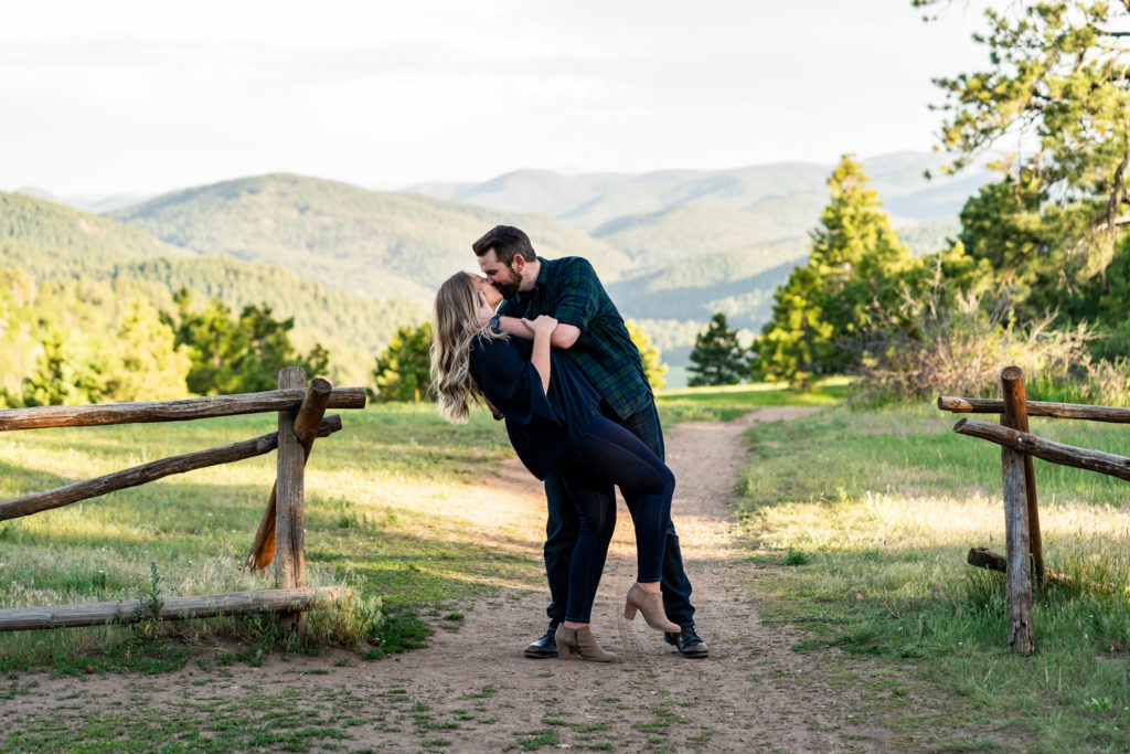 A man dipping his fiance for a kiss on a path heading toward distant mountains. Photo by Gabby Jockers Photography. Mount falcon engagement photography, colorado engagement photos, colorado engagement session, mountain engagement photos, mountain session, colorado photography, outdoor engagement photos, outdoor engagement session, hiking engagement, adventure photos, adventure session, couples photos