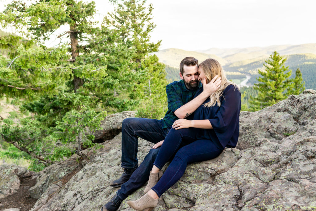 A couple sitting on a rock and snuggling up in front of a sunny mountain vista. Photo by Gabby Jockers Photography. Mount falcon engagement photography, colorado engagement photos, colorado engagement session, mountain engagement photos, mountain session, colorado photography, outdoor engagement photos, outdoor engagement session, hiking engagement, adventure photos, adventure session, couples photos