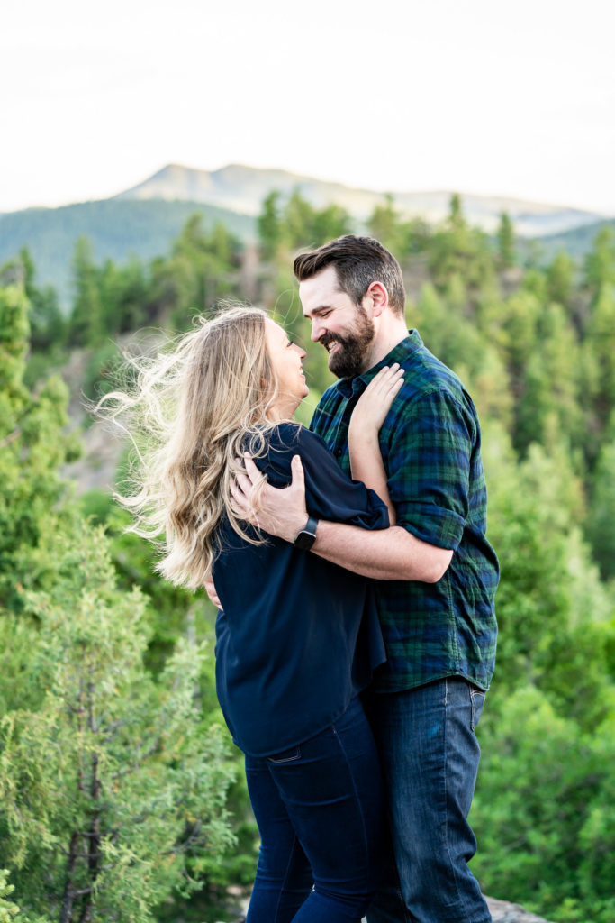 A man and woman with arms wrapped around each other in front of a mountain at sunset. Photo by Gabby Jockers Photography. Mount falcon engagement photography, colorado engagement photos, colorado engagement session, mountain engagement photos, mountain session, colorado photography, outdoor engagement photos, outdoor engagement session, hiking engagement, adventure photos, adventure session, couples photos