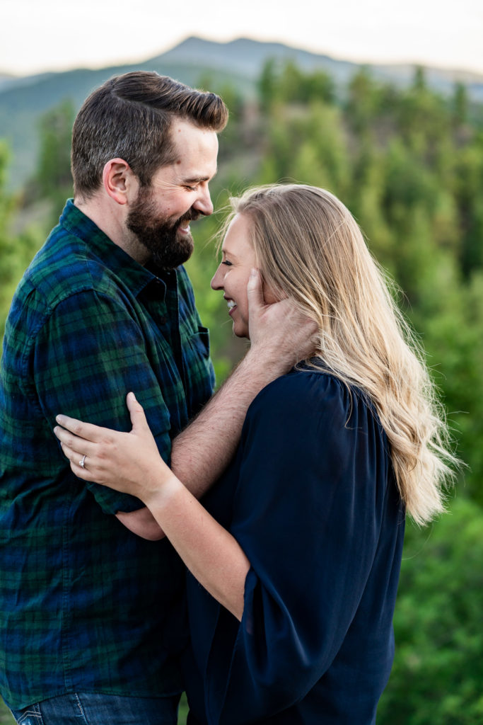 A man holds his fiance's face while they laugh together in front of a green mountain. Photo by Gabby Jockers Photography. Mount falcon engagement photography, colorado engagement photos, colorado engagement session, mountain engagement photos, mountain session, colorado photography, outdoor engagement photos, outdoor engagement session, hiking engagement, adventure photos, adventure session, couples photos