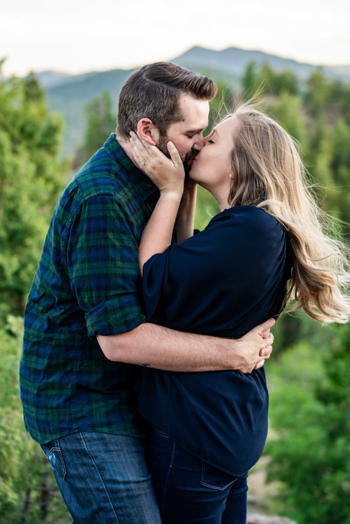 A couple in a passionate kiss and embrace in front of a green mountain. Photo by Gabby Jockers Photography. Mount falcon engagement photography, colorado engagement photos, colorado engagement session, mountain engagement photos, mountain session, colorado photography, outdoor engagement photos, outdoor engagement session, hiking engagement, adventure photos, adventure session, couples photos