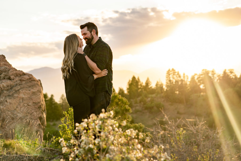 Newly engaged couple wearing dark clothes standing on a rock in front of a golden sky. Photo by Gabby Jockers Photography. Mount falcon engagement photography, colorado engagement photos, colorado engagement session, mountain engagement photos, mountain session, colorado photography, outdoor engagement photos, outdoor engagement session, hiking engagement, adventure photos, adventure session, couples photos