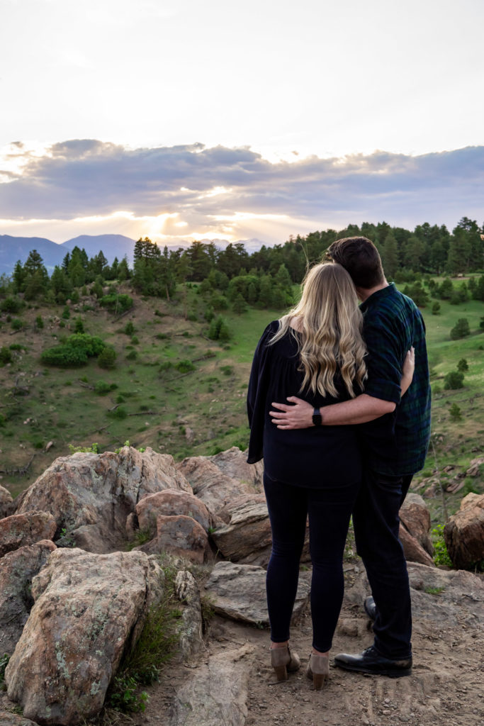 An engaged couple with arms around each other looking into the mountain sunset. Photo by Gabby Jockers Photography. Mount falcon engagement photography, colorado engagement photos, colorado engagement session, mountain engagement photos, mountain session, colorado photography, outdoor engagement photos, outdoor engagement session, hiking engagement, adventure photos, adventure session, couples photos